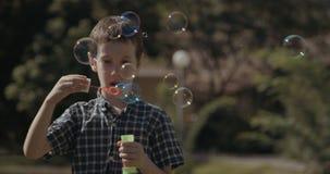 Bulles de savon de soufflement de jeune garçon dehors banque de vidéos