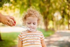 Bulles de savon de soufflement de petite fille Images stock