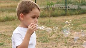 Bulles de savon de soufflement de bébé heureux Les bulles volent dans le vent dans le mouvement lent, en gros plan clips vidéos