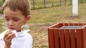 Bulles de savon de soufflement d'enfant heureux dans le mouvement lent, en gros plan clips vidéos