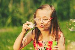 Bulles de savon de soufflement d'enfant de petite fille extérieures Photo stock