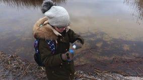 Bulles de savon de soufflement de fille près du lac banque de vidéos