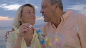 Bulles de soufflement de couples supérieurs au bord de la mer banque de vidéos