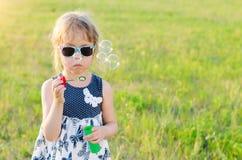 Bulles de soufflement de fille mignonne en parc, l'espace libre Image stock