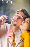 Bulles de soufflement de jeunes couples photo stock