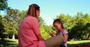 Bulles de soufflement de petite fille à sa mère en parc clips vidéos