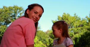 Bulles de soufflement de petite fille à sa mère heureuse en parc banque de vidéos