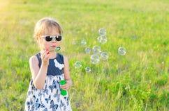 Bulles de soufflement de petite fille en parc, l'espace libre Image libre de droits