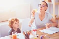 Bulles de soufflement heureuses de mère et de fils image stock