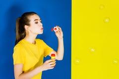 Bulles de soufflement de jeune femme heureuse sur le bleu photos libres de droits