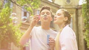 Bulles et étreindre de savon de soufflement de couples gais, dupant autour, souvenirs d'amour banque de vidéos