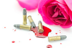 Bullet on blood and red rose on white background Stock Images