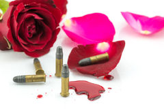 Bullet on blood and red rose on white background Stock Photo