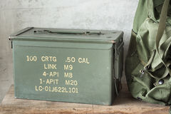 Bullet box with backpack. Old and dusty bullet box ( ammo crate ) with part of backpack Stock Photo
