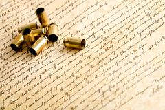 Bullet casings on bill of rights. Bullets on the bill of rights - the right to bear arms - spent casings, macro with focus on rightmost casing Stock Photos