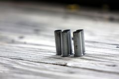 Bullet casings. Used bullet casings sitting on wood table Royalty Free Stock Photography