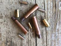 Bullet casings from a variation of guns and rifles. On a wooden background royalty free stock image