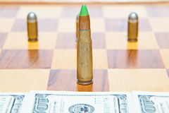 Bullet instead of chess piece. Concept of military power.  Royalty Free Stock Photo