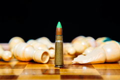 Bullet instead of chess piece. Concept of military power. Closeup photo of one bullet standing on chessboard among lying chess pieces Stock Images