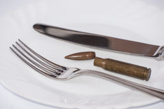 Bullet disassembled. Fork plate and knife Stock Photography
