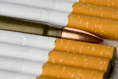 Bullet among filtertipped cigarettes Royalty Free Stock Images