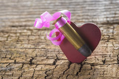 Bullet with a heart decorated like a gift. On a wooden background Royalty Free Stock Image
