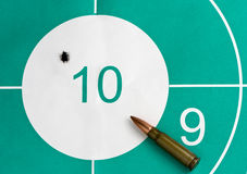 Bullet hit the target. Close-up of cartridge and bullseye with bullet hole Royalty Free Stock Photography