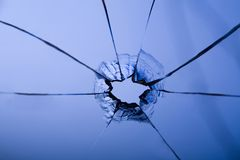 Bullet hole. In glass on blue with crack Stock Photos