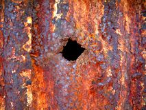 Bullet Hole. A bullet hole though an old rusty shed Royalty Free Stock Photo