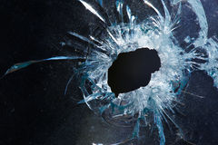 A bullet hole is in glass. Photo broken window looks like a bullet hole Stock Images