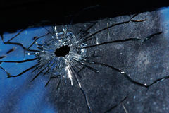 A bullet hole is in glass. Photo broken window looks like a bullet hole Royalty Free Stock Photography