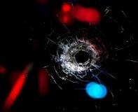 Bullet hole in the glass. Bullet hole in the glass on  black background Royalty Free Stock Image