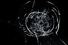 Bullet hole in glass close up on black background. Bullet hole in glass closeup on black background Royalty Free Stock Images