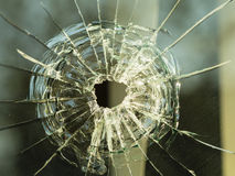 Bullet hole on glass making cracks Royalty Free Stock Images