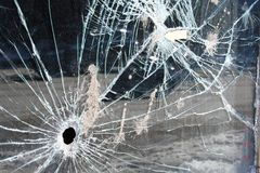 Bullet hole in glass window. A hole apparently made from a gunshot Royalty Free Stock Photo