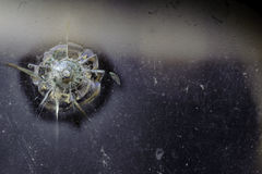 Bullet hole in old truck window. At junk yard Stock Images