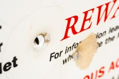 Bullet Hole in sign. Bullet hole through a sign offering reward Stock Photography