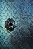 Bullet hole in window. A cracked and broken blue-tinted window with what looks like a bullet hole Stock Images