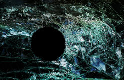 Bullet hole window. Bullet hole in cracked glass window Stock Images
