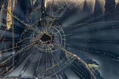Bullet Hole, Broken Glass, Window, Shattered. Bullet hole in window glass. The shattered remains have broken the pane and left cracks Royalty Free Stock Image