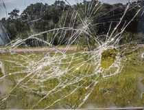 Bullet hole through a window shattering the glass. Horizontal image of a bullet hole through a window causing it to shatter over the whole window Royalty Free Stock Image