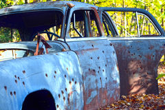 Bullet Holes in a Junk Car. An abandoned car filled with bullet holes Stock Photo
