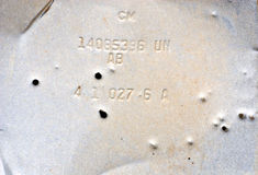 Bullet Holes in an Old Piece of Metal. Gray, grungy piece of old metal with random numbers and letters, riddles with bullet holes Royalty Free Stock Photos
