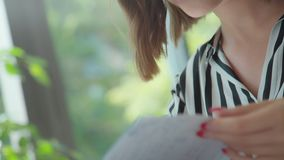 Bullet Journal: girl flips through the pages of the diary. Close-up: women`s hands flipping through a diary with a bookmark, details. Bullet Journal: a girl with stock footage