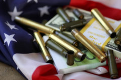 Bullet and money on the american flag Royalty Free Stock Photo