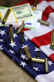Bullet and money on the american flag Stock Photography