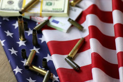 Bullet and money on the american flag Royalty Free Stock Image