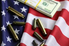 Bullet and money on the american flag Royalty Free Stock Images