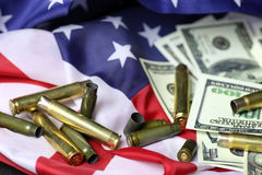 Bullet and money on the american flag Stock Photos