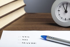 Bullet pen, books,  clock, Yes No Maybe decision. Blue bullet pen, stack of books, clock and an sheet of paper showing Yes No Maybe decision question Stock Image